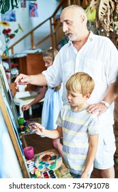 Portrait of senior teacher helping little boy painting picture in art studio standing by easel with other children in background