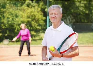 Portrait of senior tennis coach standing at net while playing tennis with elderly woman.