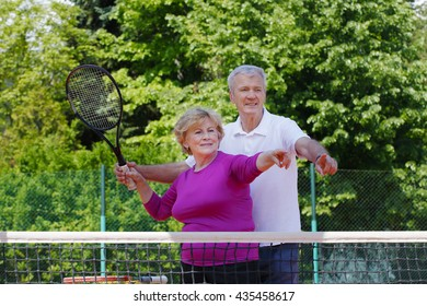 Portrait of senior tennis coach teaching to serving active elderly woman while standing at net on tennis court.