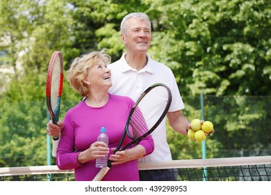 Portrait of senior tennis trainer and elderly woman standing at net in tennis court after playing match.