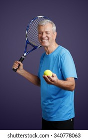 Portrait of senior tennis trainer standing against isolated background while holding in his hand a tennis racket and tennis ball.