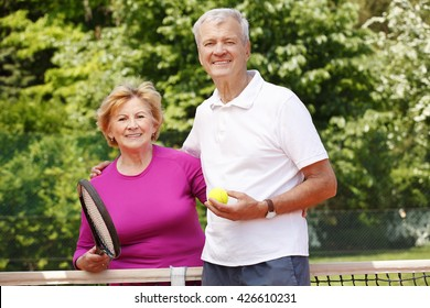 Portrait of senior tennis trainer standing at net with elderly woman after tennis match.
