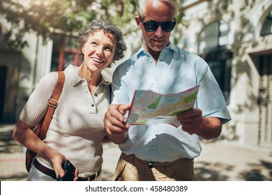 Portrait of senior tourist couple in town using a map. Mature man and woman using map while sightseeing.