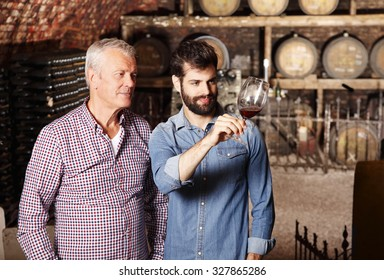 Portrait of senior vintner and young winemaker tasting the new wine. Business people working together at winery. Small business.