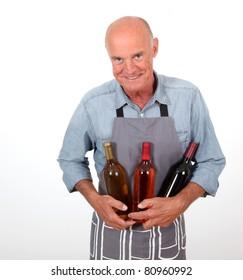 Portrait of senior winemaker holding bottles of wine