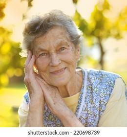 Portrait of senior woman in apron in the sunny garden