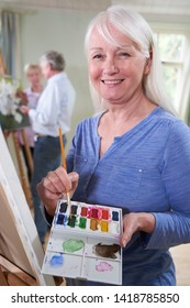 Portrait Of Senior Woman Attending Painting Class With Teacher          In Background