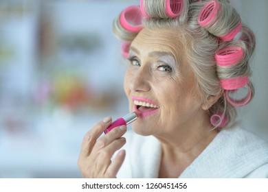 Portrait of senior woman in bathrobe with lipstick