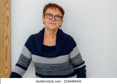 Portrait of senior woman with blue sweater and fashionable glasses.