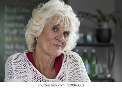 Portrait of a senior woman in a cafe, looking at the camera