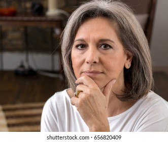 Portrait of a senior woman, confident, looking at camera, 60 years old, grey hair, hand on chin.