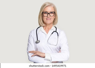 Portrait of senior woman doctor wearing glasses and uniform stand isolated on grey studio background, mature female medical nurse or practitioner with stethoscope look at camera. Healthcare concept