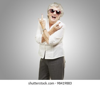 portrait of a senior woman doing a rock symbol against a grey background