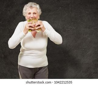 portrait of senior woman eating vegetal sandwich against a grunge wall