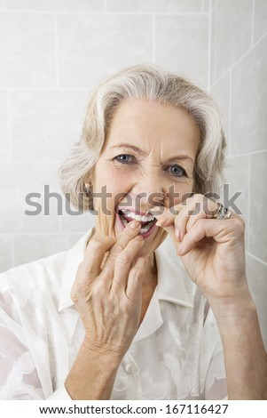 Portrait of senior woman flossing teeth in bathroom