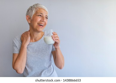 Portrait of a senior woman with a glass of milk. Beautiful elderly woman in grey T-shirt with a glass of milk on a grey background. Senior woman drinking milk at home