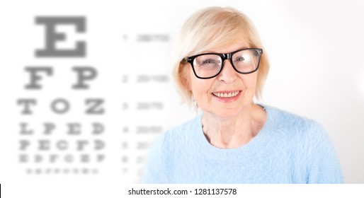 Portrait of senior woman in glasses, having eye on the vision testing tables background. Visiting a doctor ophthalmologist.