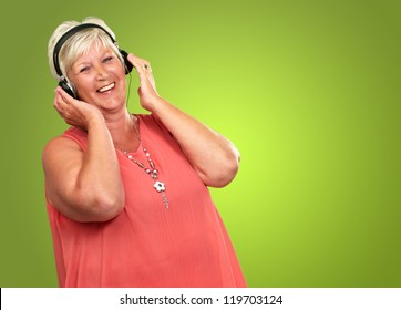 Portrait Of A Senior Woman With Headphone On Green Background