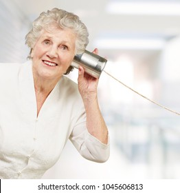portrait of senior woman hearing with metal tin can indoor