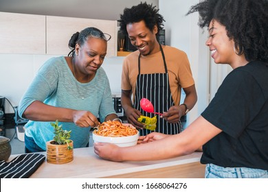 Portrait of senior woman helping daughter and son in law to cook at home. Family and lifestyle concept.