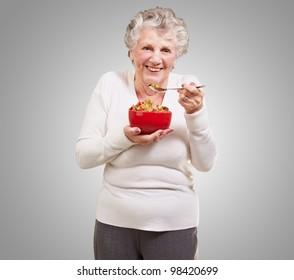 portrait of a senior woman holding a cereal bowl against a grey background