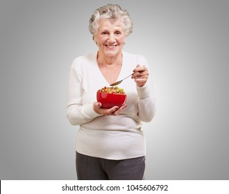 portrait of senior woman holding a cereals bowl against a grey background