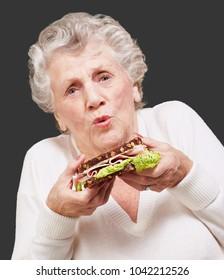 portrait of senior woman holding a delicious sandwich over black background