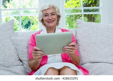 Portrait of senior woman holding digital tablet on sofa