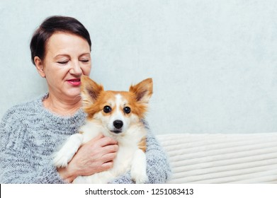 Portrait of senior woman holding her dog on sofa