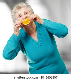 portrait of senior woman holding a orange slice in front of her mouth, indoor