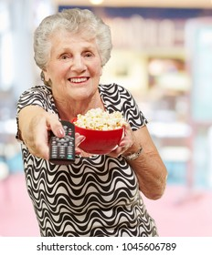 portrait of senior woman holding pop corn bowl and changing channel of tv indoor