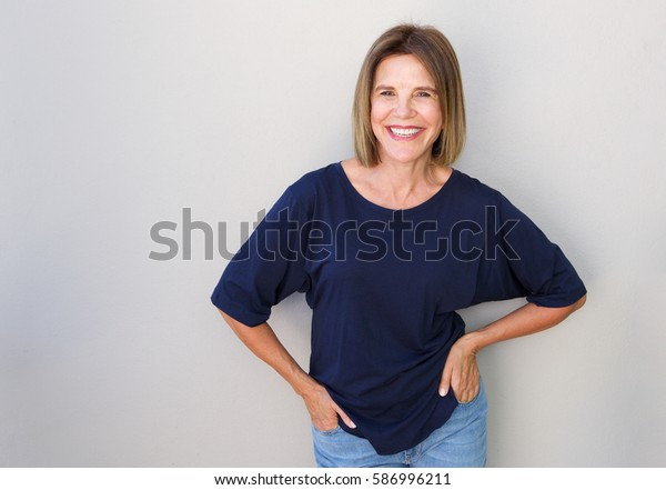 Portrait of senior woman laughing against gray wall
