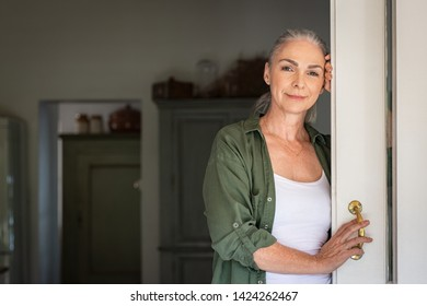 Portrait of senior woman leaning against door at home and looking at camera. Smiling mature woman standing at doorway and looking at camera. Portrait of old lady relaxing and thinking with copy space.