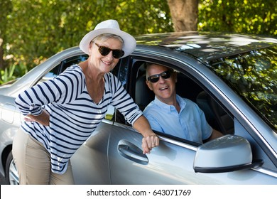Portrait of senior woman leaning while man sitting in car