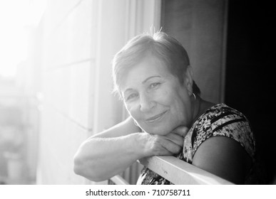 Portrait of senior woman looking from the balcony