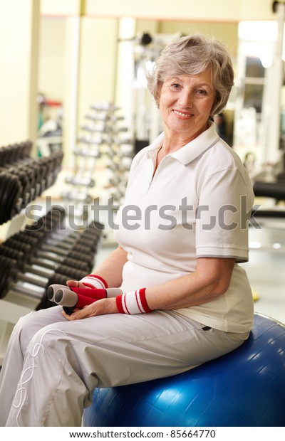 Portrait of senior woman looking at camera and smiling in gym