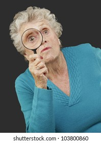 portrait of a senior woman looking through a magnifying glass over a black background