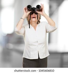 portrait of senior woman looking through a binoculars , indoor