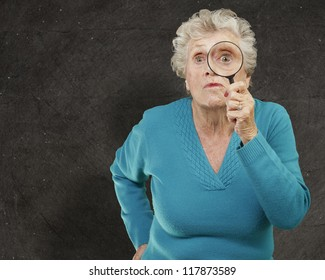 portrait of senior woman looking through a magnifying glass against a grunge wall