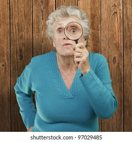 portrait of senior woman looking through a magnifying glass against a wooden wall