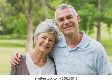 Portrait of a senior woman and man with arms around at the park