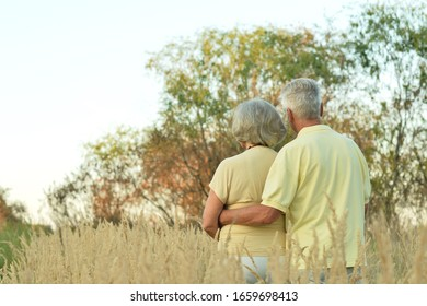 Portrait of senior woman and man in park. Back view
