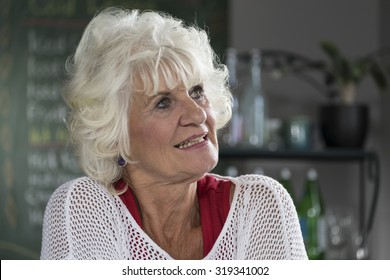 Portrait of a senior woman n a cafe, looking over her shoulder