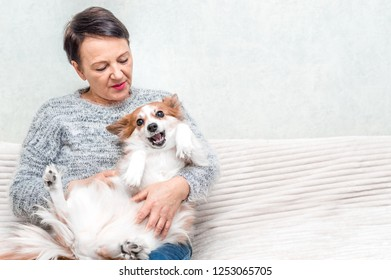Portrait of senior woman play with her dog on sofa
