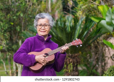 Portrait of senior woman playing ukulele in her garden. The music and musical instrument makes very happy old woman and good mental health. Health care concept