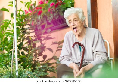 Portrait of senior woman poking out tongue