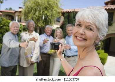 Portrait of senior woman recording happy moments with friends