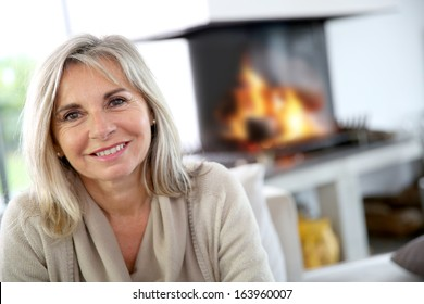Portrait of senior woman relaxing by fireplace