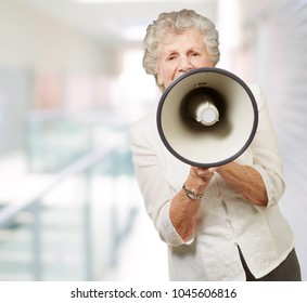 portrait of senior woman screaming with megaphone at modern place