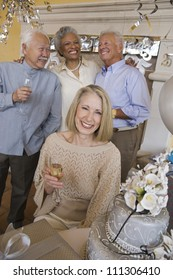 Portrait of senior woman sitting with glass of champagne with friends in the background